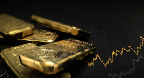 Gold bars on black back ground with line graph representing stock market